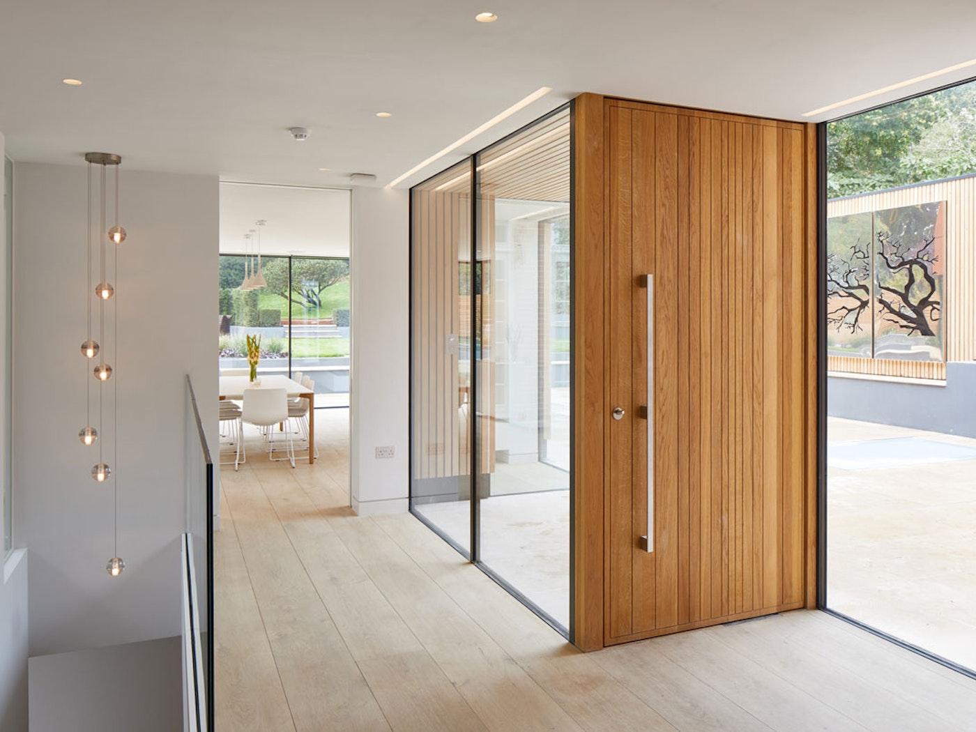 Neo oversized pivot front door | vertical grooves | European Oak | Option 11 handle