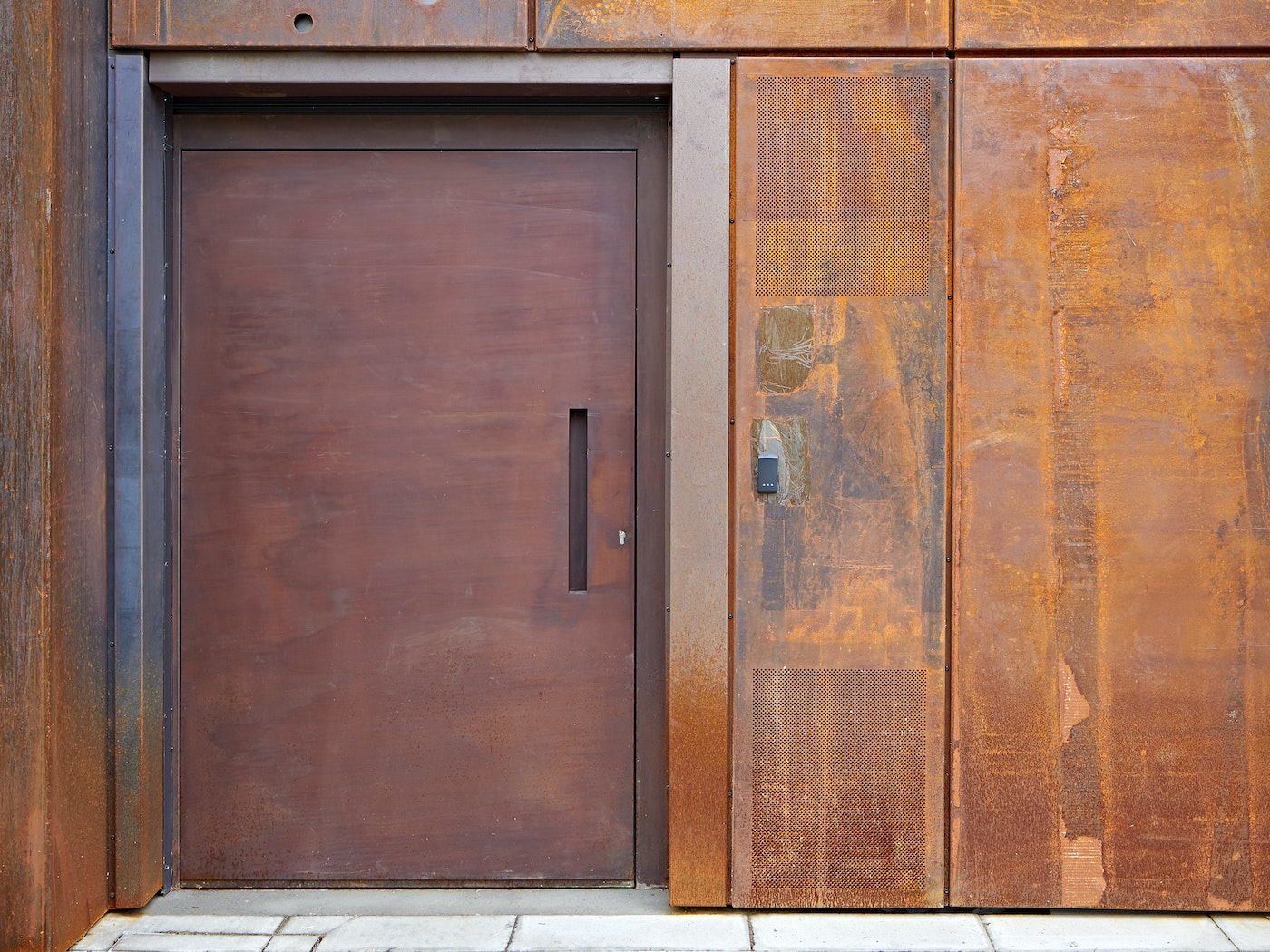 """""""Raw"""" steel door in a rust (corten) finish on a commercial building in London"""
