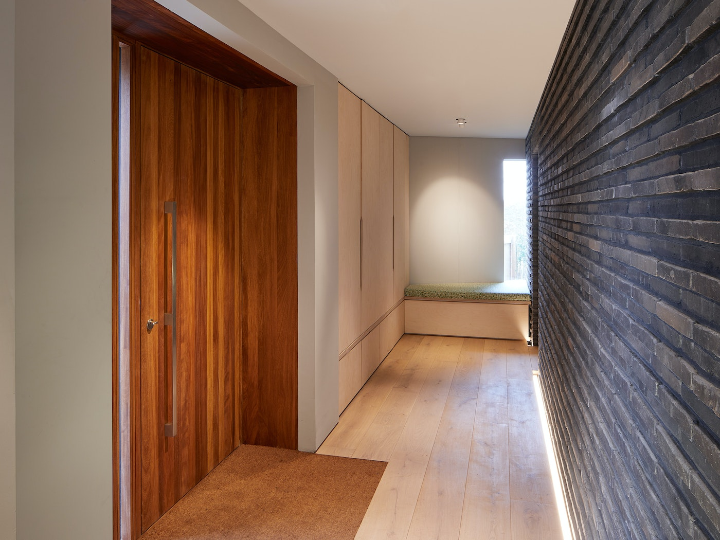 The Iroko door sits opposite a brick wall with similar raised elements works perfectly together