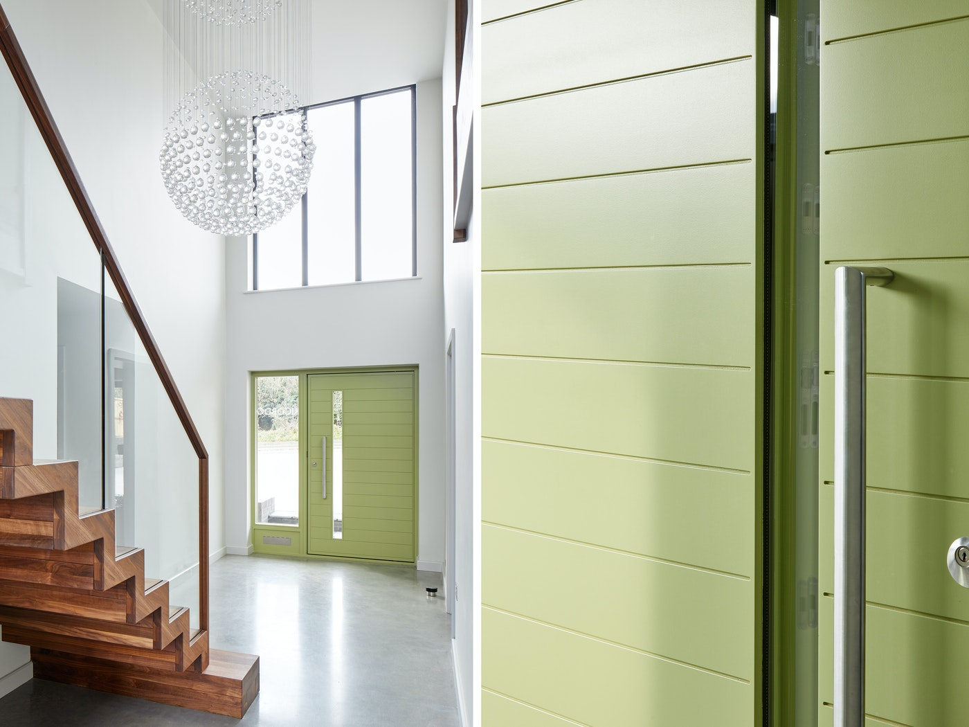 The clean white interior is the perfect base to show off the bold green door and rich walnut staircase